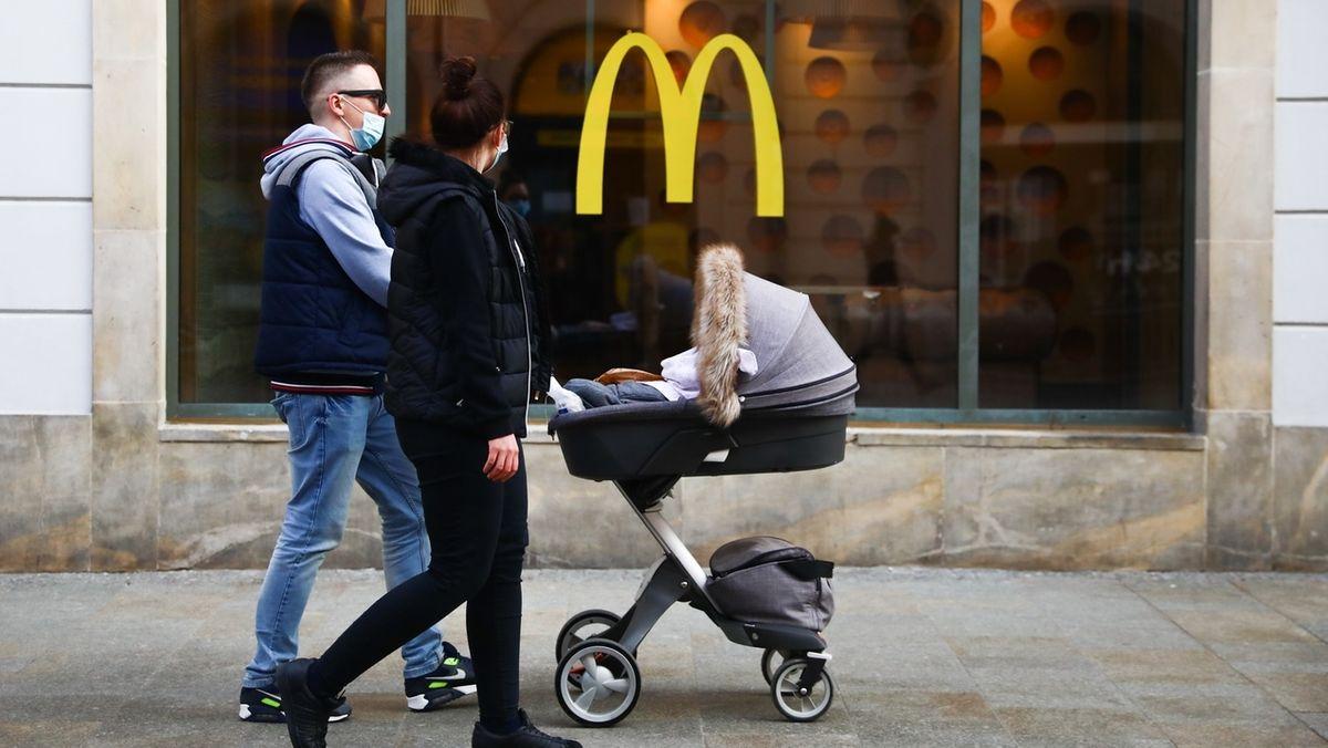 Ein junges Paar mit Kinderwagen läuft an einem Schaufenster vorbei an dem das gelbe M der Fastfood-Kette McDonald's prangt.