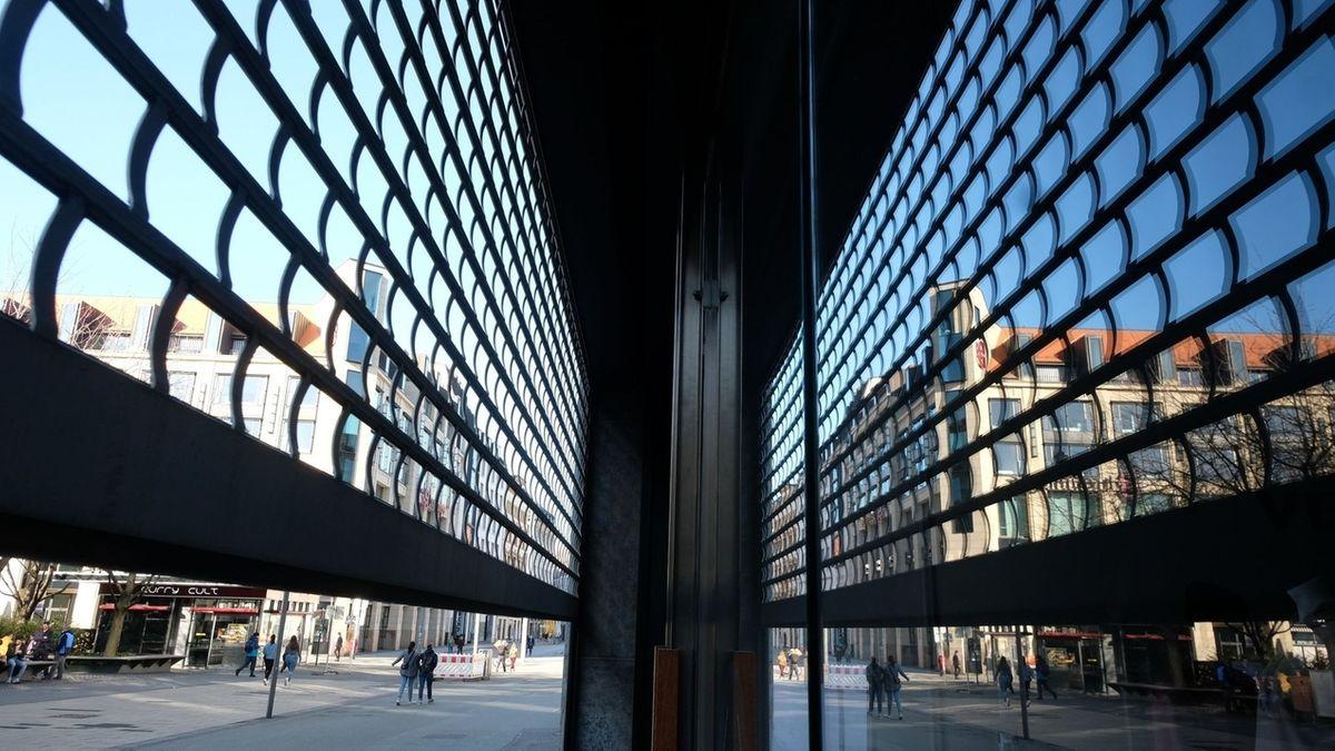 Das Gitter eines Schaufensters an einem Ladengeschäft im Stadtzentrum ist zur Hälfte heruntergelassen.