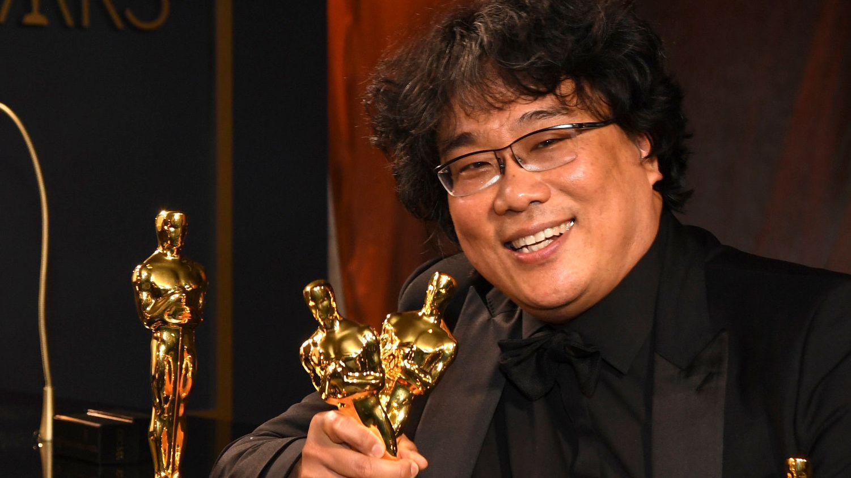 Regisseur Bong Joon Ho hält mehrere Oscar-Statuen in der Hand und blickt lachend in die Kamera