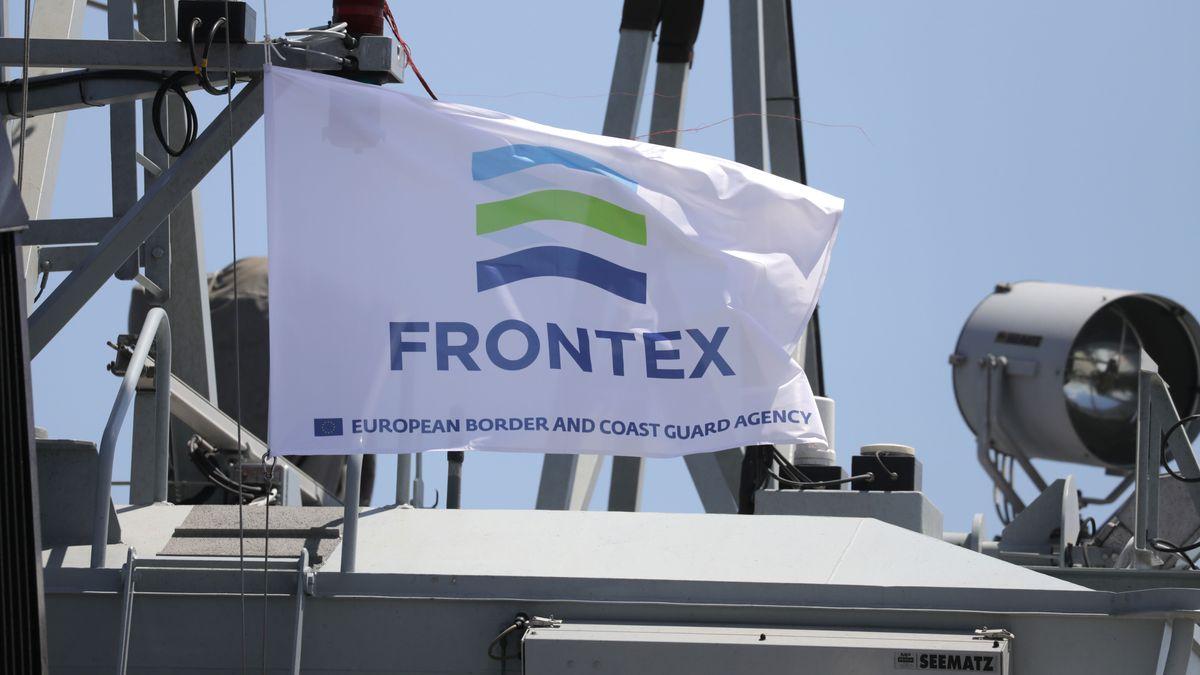 Eine Frontex-Flagge weht an einem Gestänge auf einem Militärboot. Daneben ein Scheinwerfer.