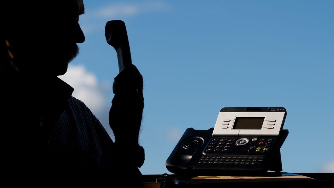 Ein Mann im Schatten hält einen Telefonhörer in der Hand, neben ihm steht ein Telefon