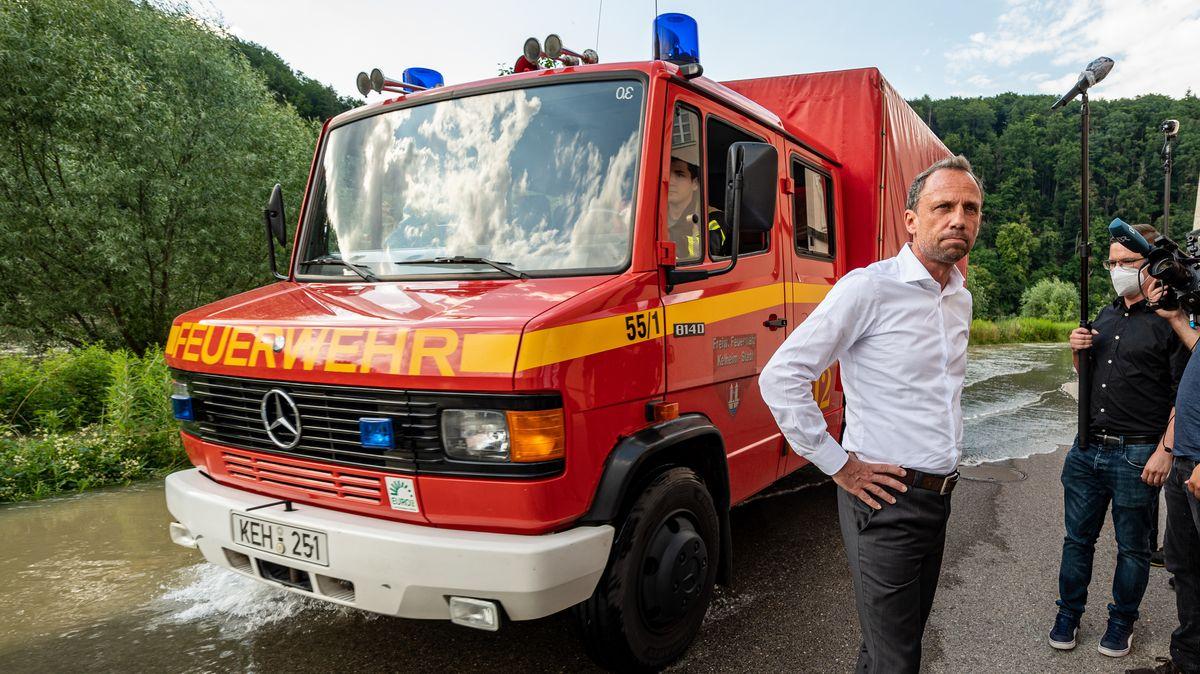 Bayerns Umweltminister Glauber vor einem Feuerwehrauto an der Hochwasser führenden Donau vor dem Kloster Weltenburg.