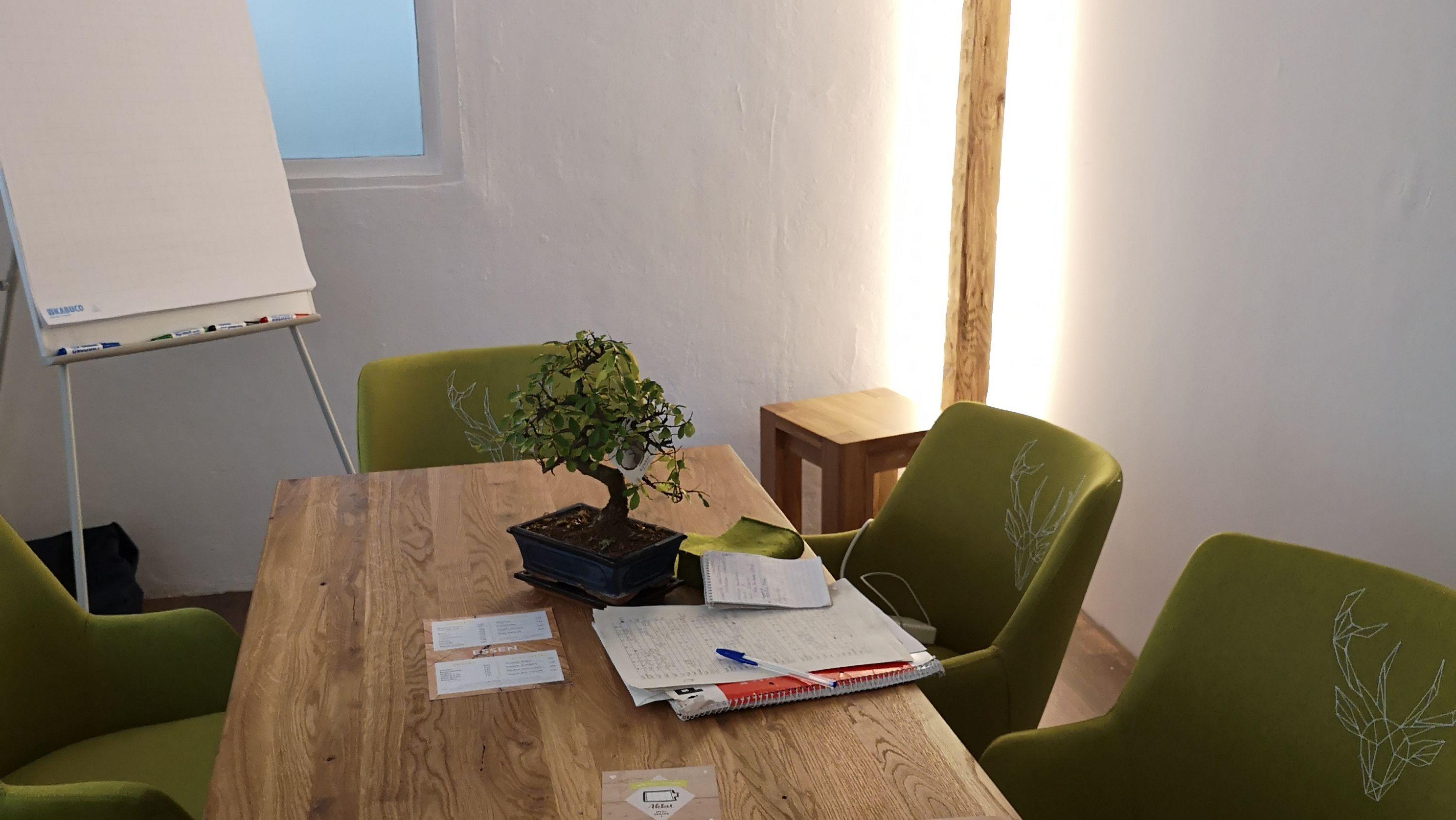 Ein Seminarraum mit grünen Stühlen, einem Holztisch und einem Whiteboard.