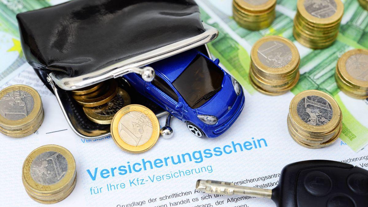 Geldmünzen auf Kfz-Versicherungsschein.