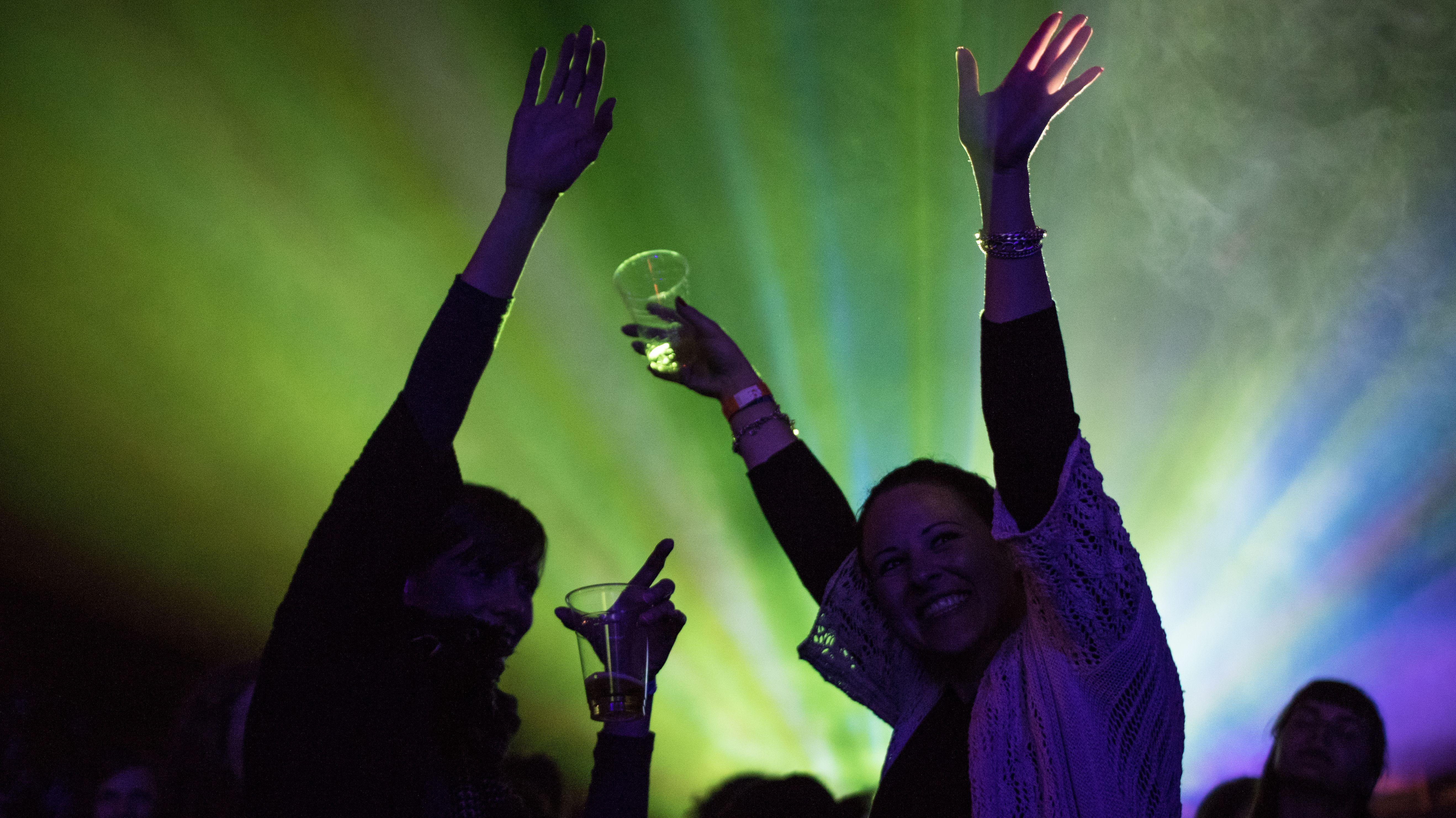 Zwei feiernde Frauen im Dunkeln mit bunten Scheinwerfern