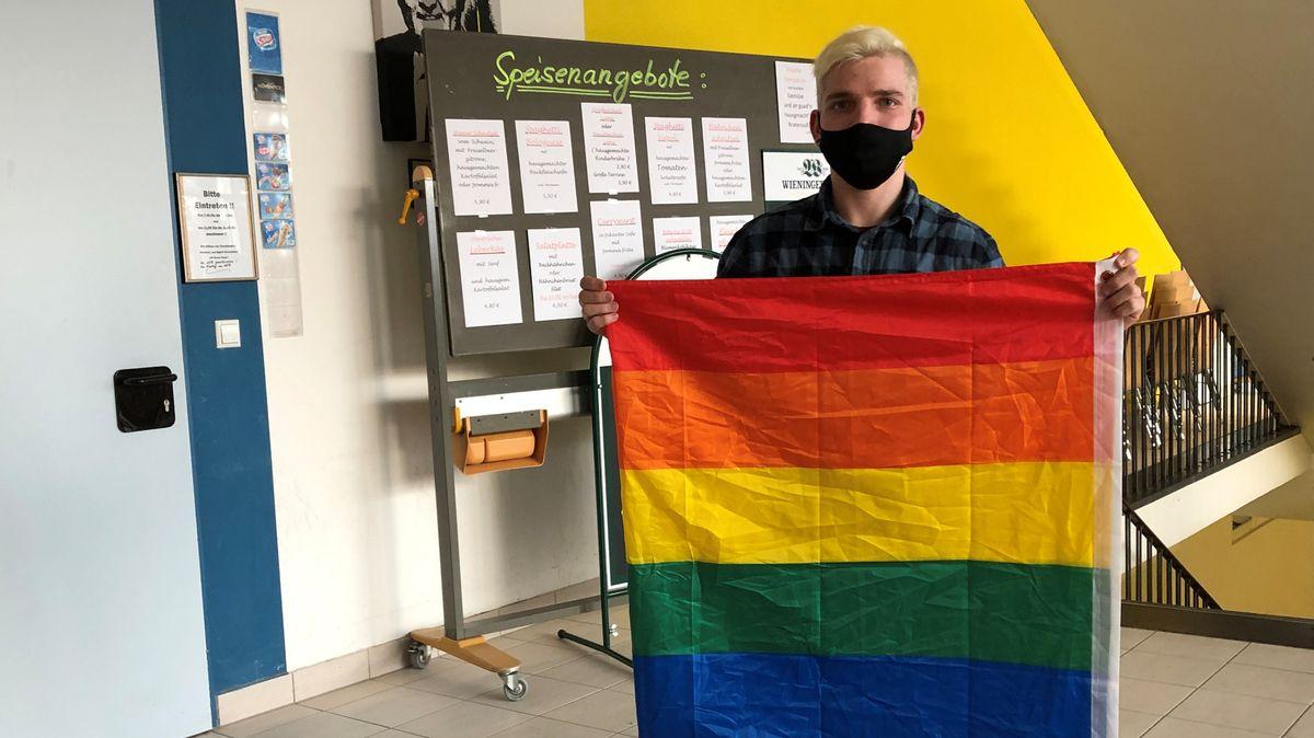 Der 19-jährige Justin Lorenz hält eine Regenbogenfahne in der Aula der Berufsschule in Freilassing hoch.