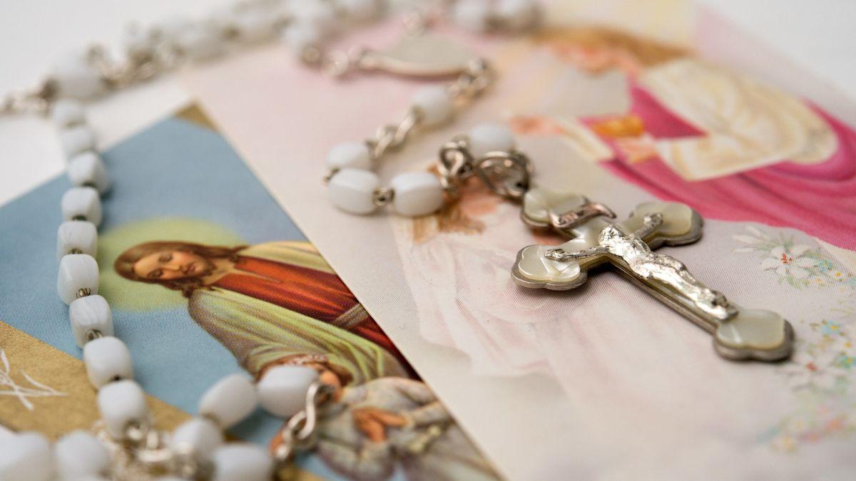 Ein weißer Kommunions-Rosenkranz liegt auf katholischen Heiligenbildchen.