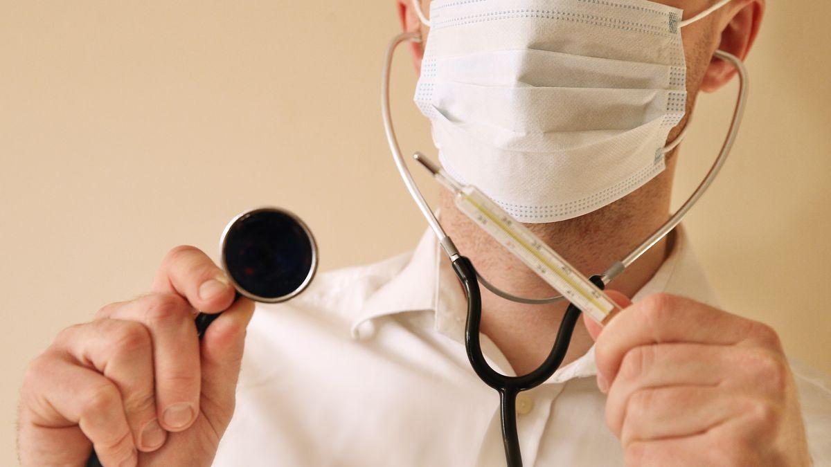 Mann mit Mundschutz, Stethoskop und Thermometer (Symbolbild)
