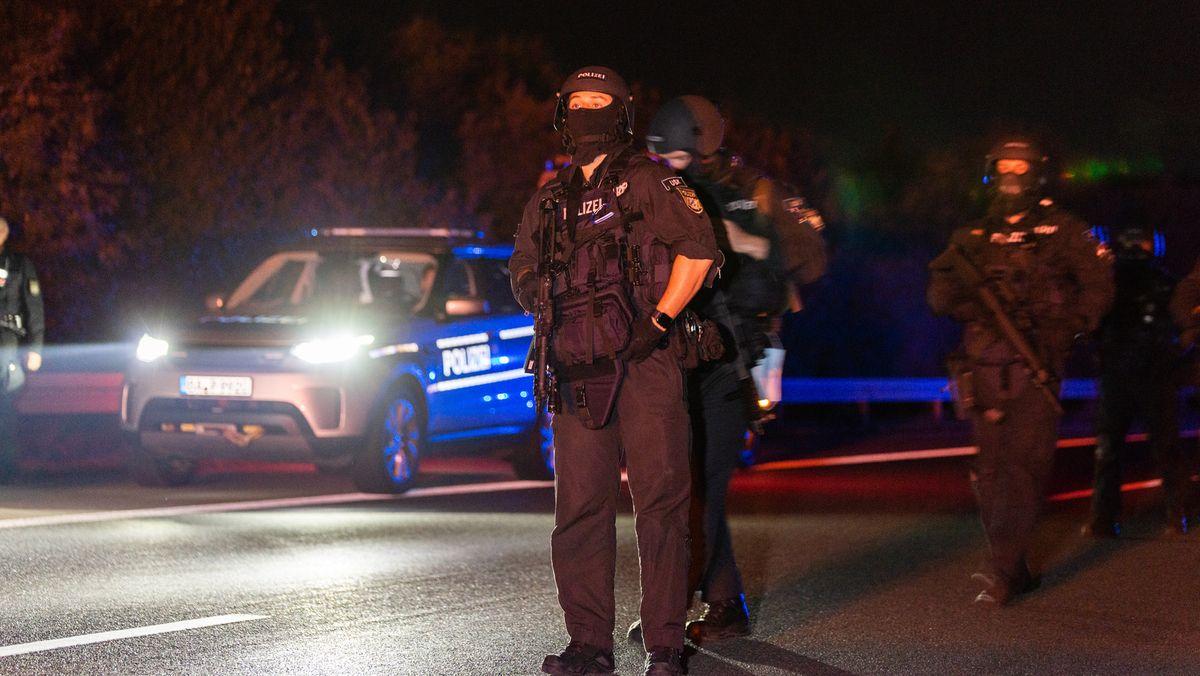 Vermummte SEK-Polizeibeamte neben einem Polizeiauto.