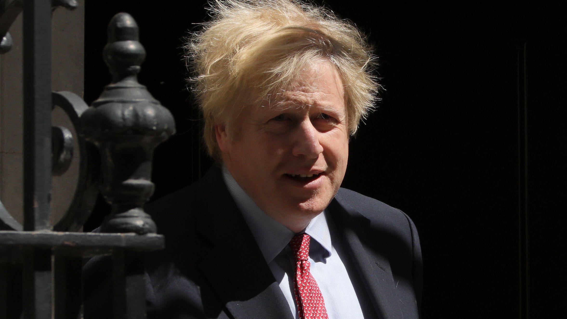 Boris Johnson kommt aus der Haustür seines Amtssitzes und geht an einem Gitter vorbei.