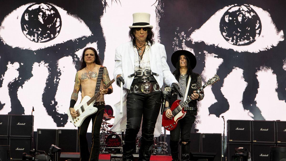 Alice Cooper performt mit zwei Gitarristen auf der Bühne.