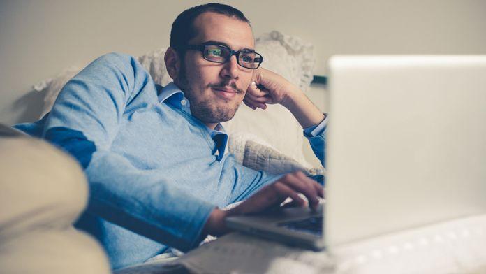 Symbolbild: Mann schaut von daheim aus einen Online-Gottesdienst auf dem Laptop
