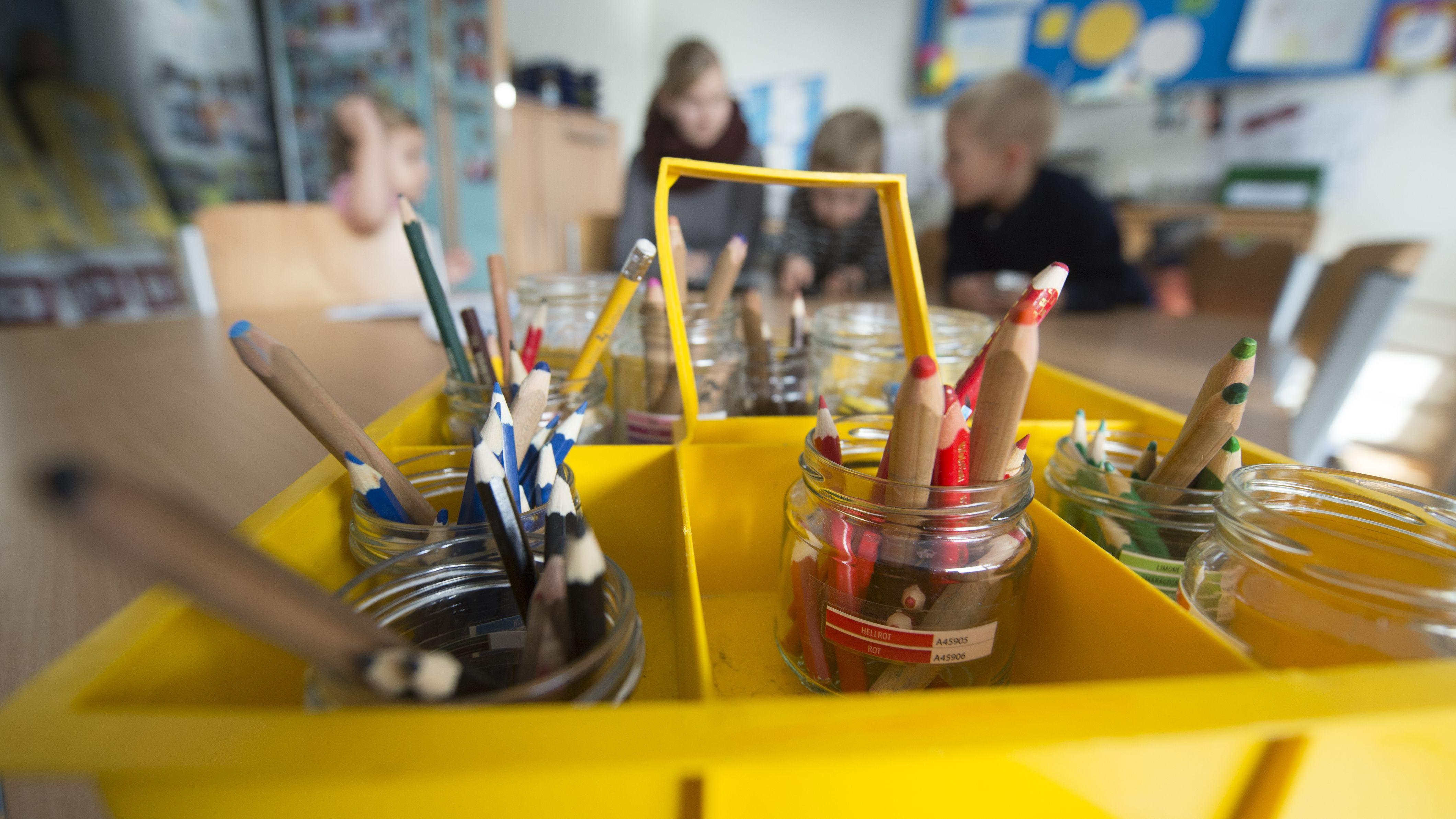 Blick in eine Kita: Stifte im Vordergrund, Kinder im Hintergrund.