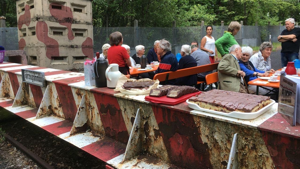 Senioren aus Mellrichstadt sind zu Gast am ehemaligen Grenzübergang Eußenhausen-Meiningen. Sie sitzen auf Bierbänken und unterhalten sich.