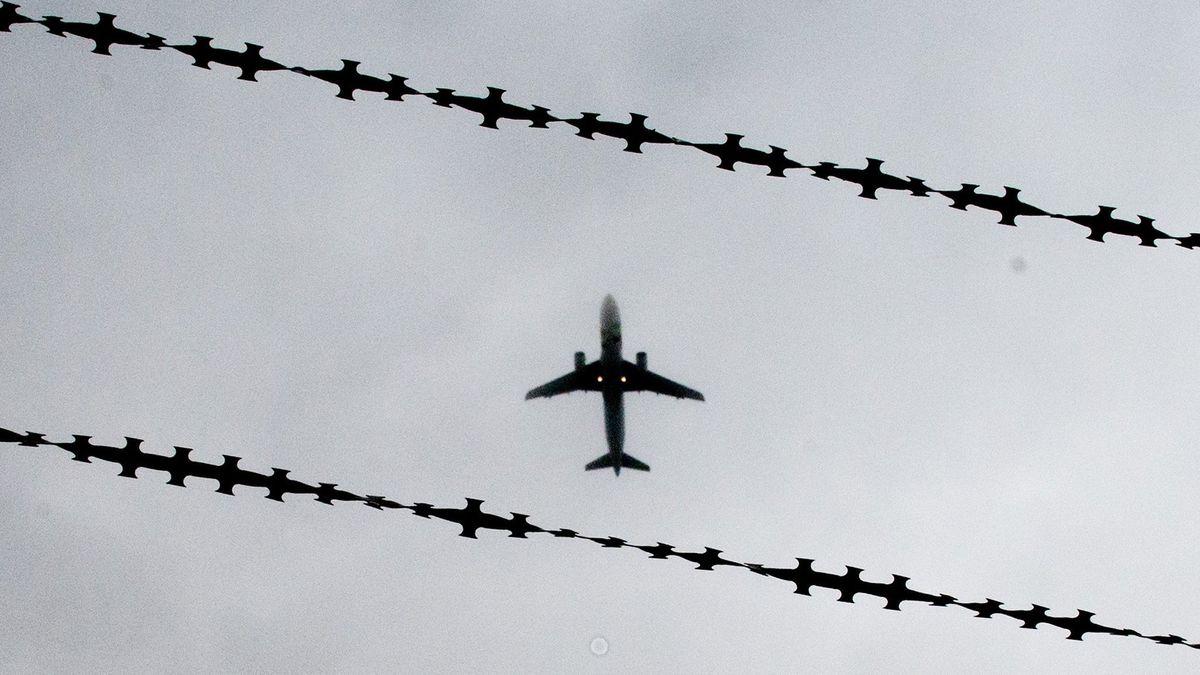 Flugzeug in der Luft zwischen Stacheldraht.