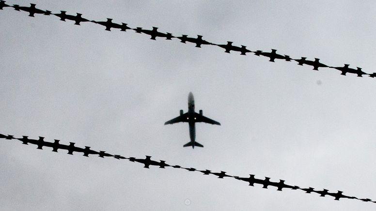 Flugzeug in der Luft zwischen Stacheldraht. | Bild:dpa-Bildfunk/Julian Stratenschulte