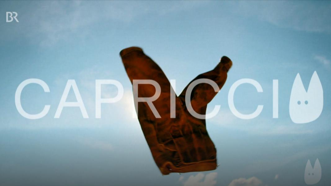 Eine Lederhose vor weiß-blauem Himmel, darüber der Schriftzug Capriccio