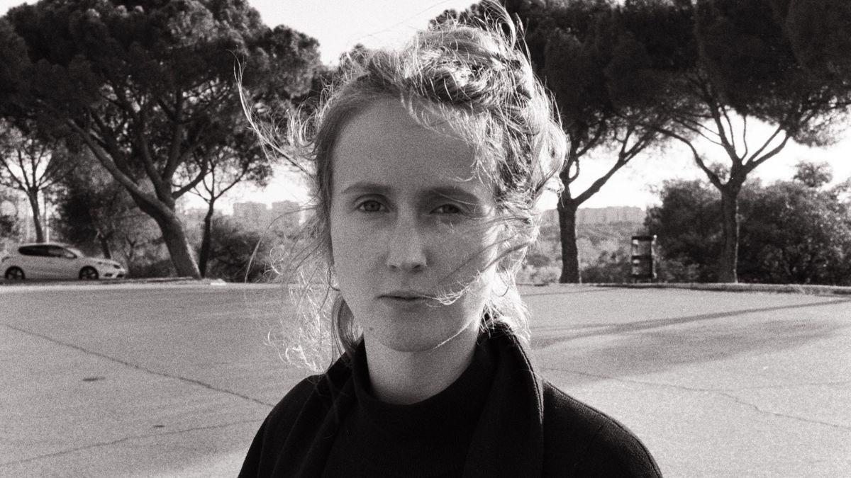 Schwarzweißporträt einer jungen Frau auf einem Parkplatz