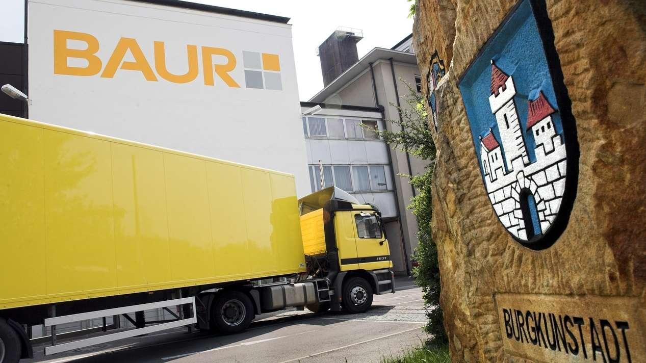 Ein Lkw von Baur Versand fährt auf das Firmengelände. Auf der rechten Seite ist das Wappen von Burgkunstadt auf einer Mauer zu sehen.
