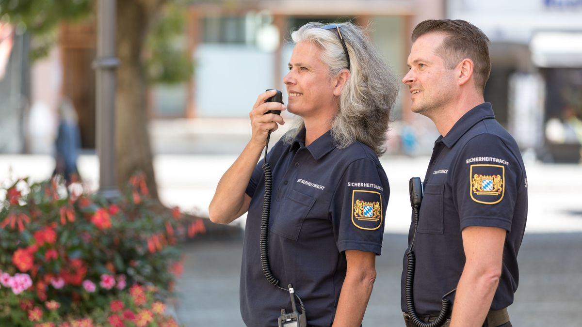 Eine Frau und ein Mann in Uniform der Sicherheitswacht.