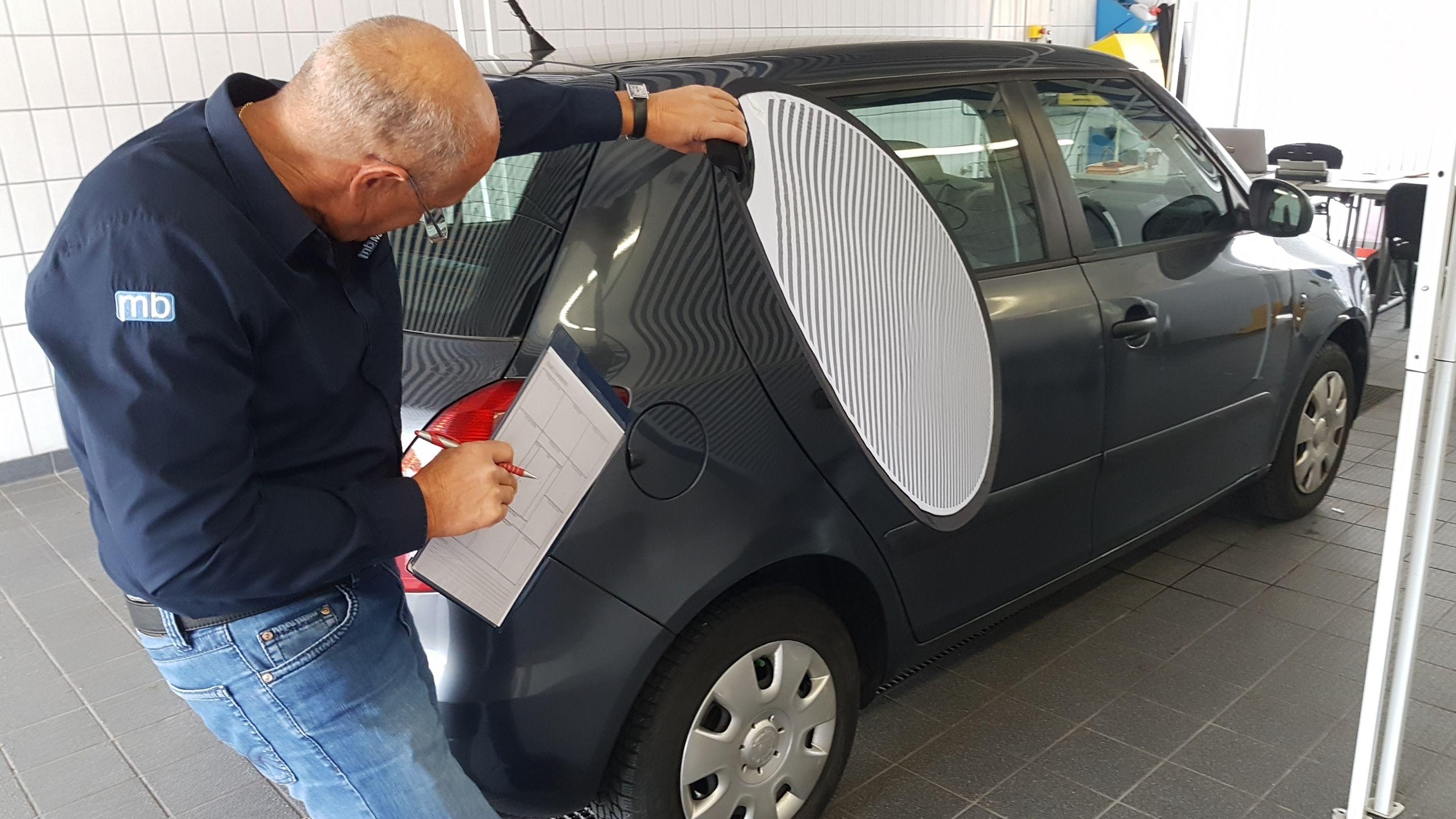 """Ein Gutachter prüft mit einem sogenannten """"Dellenreflektor"""" ein Auto auf Hagelschaden"""