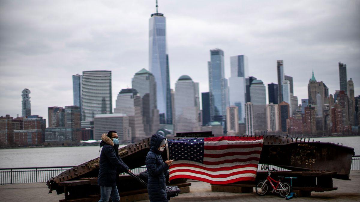 Menschen mit Masken gehen vor der Skyline von New York spazieren