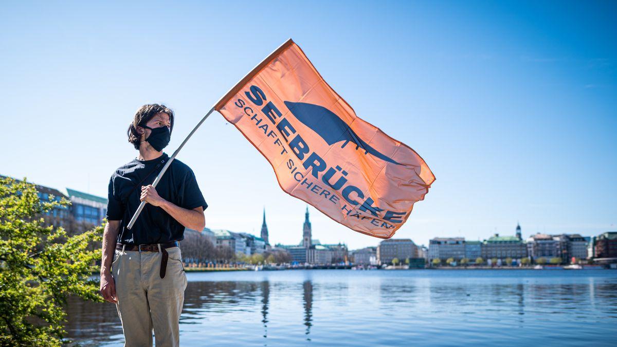 Mann vor Wasser mit Flagge in der Hand mit dem Titel: Seebrücke Schafft sichere Häfen