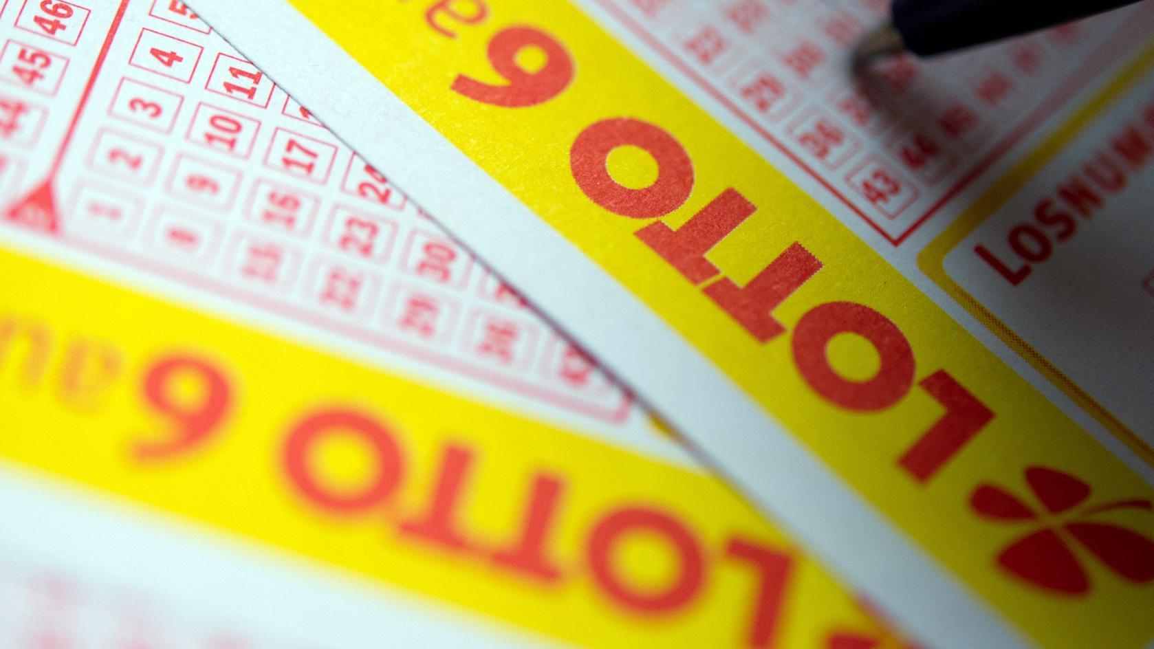 Baden-Württemberg, Stuttgart: Ein Mann füllt einen Lottoschein aus.