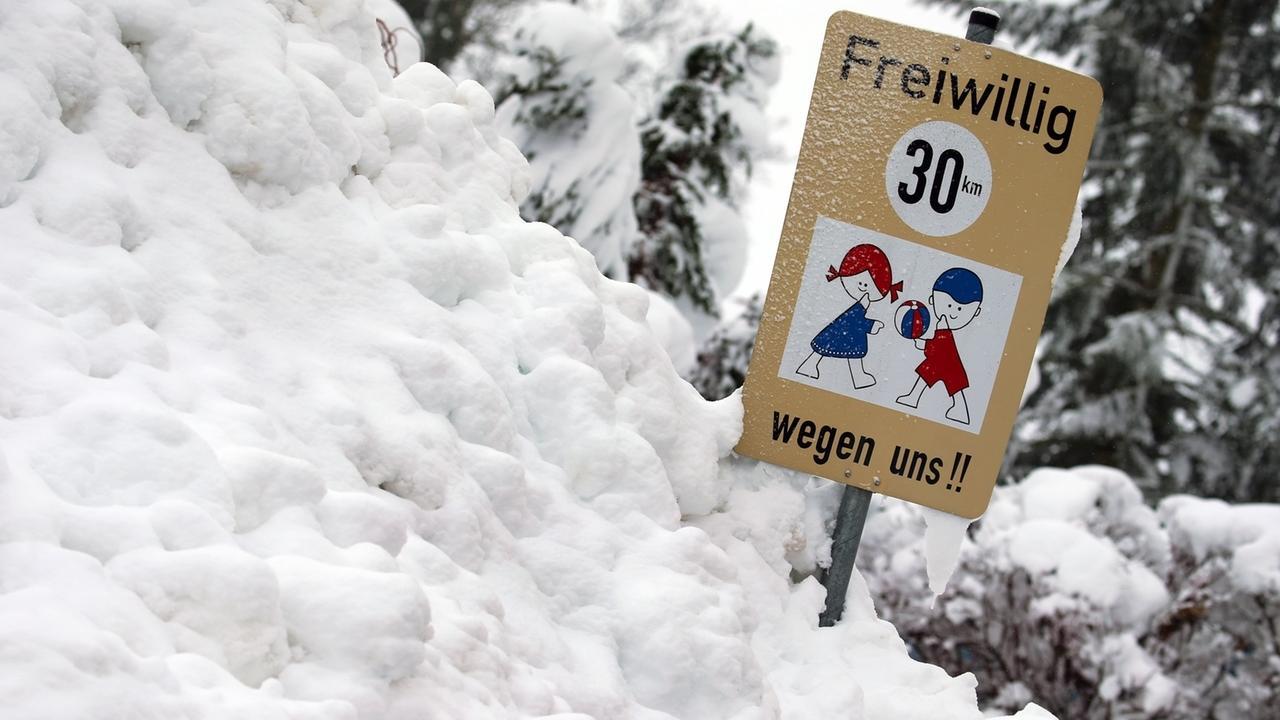 Ein Hinweisschild auf spielende Kinder steht in einem Schneehaufen.