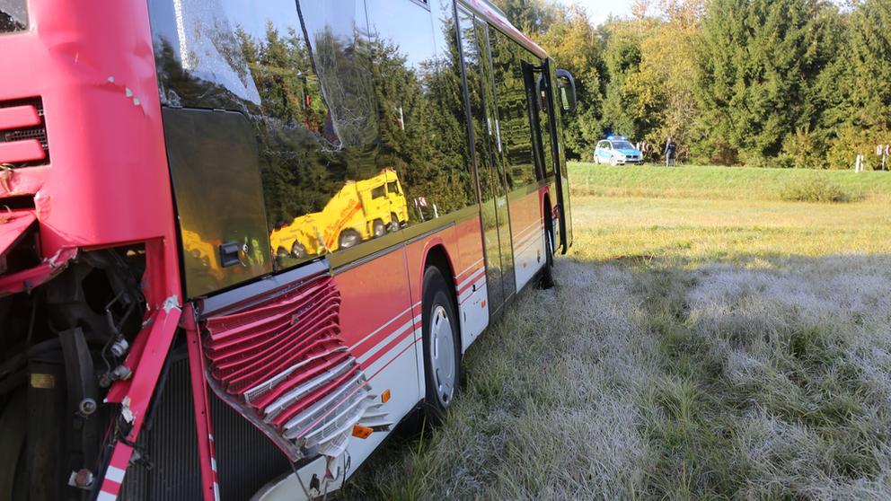 Ein demolierter roter Schulbus steht auf einer Wiese abseits der Straße.   Bild:News5