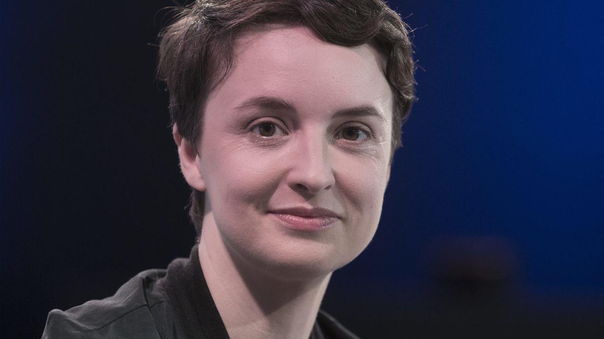 Schriftstellerin Katharina Adler blickt vor dunklem Hintergrund lächelnd in die Kamera