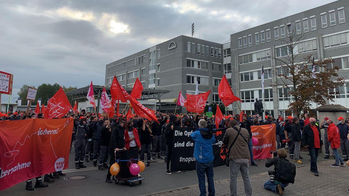 Menschen mit roten IG Metall-Fahnen vor dem MAN-Werk in Nürnberg.