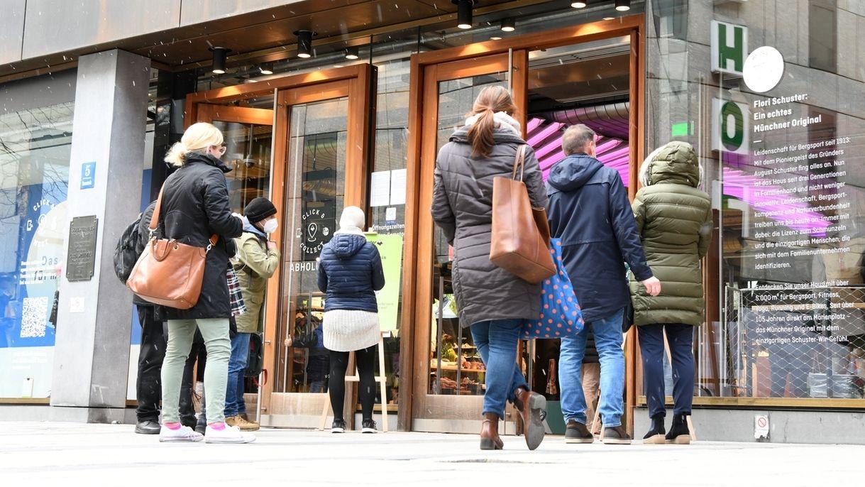 Symbolbild: Kunden warten vor einem Laden in München auf Einlass