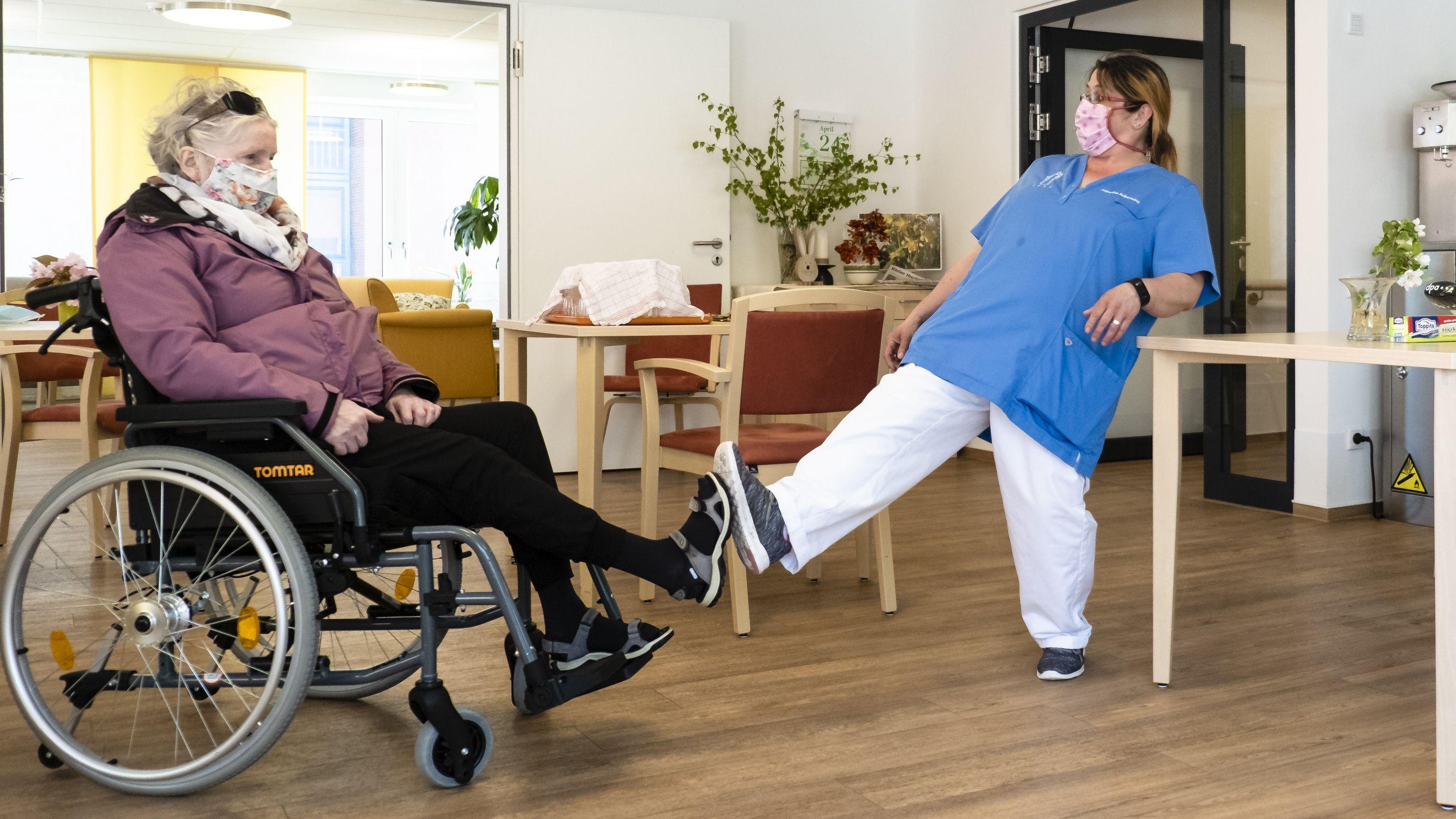 Eine Altenpflegerin und eine Bewohnerin einer Pflegeeinrichtung begrüßen sich per Fuß.