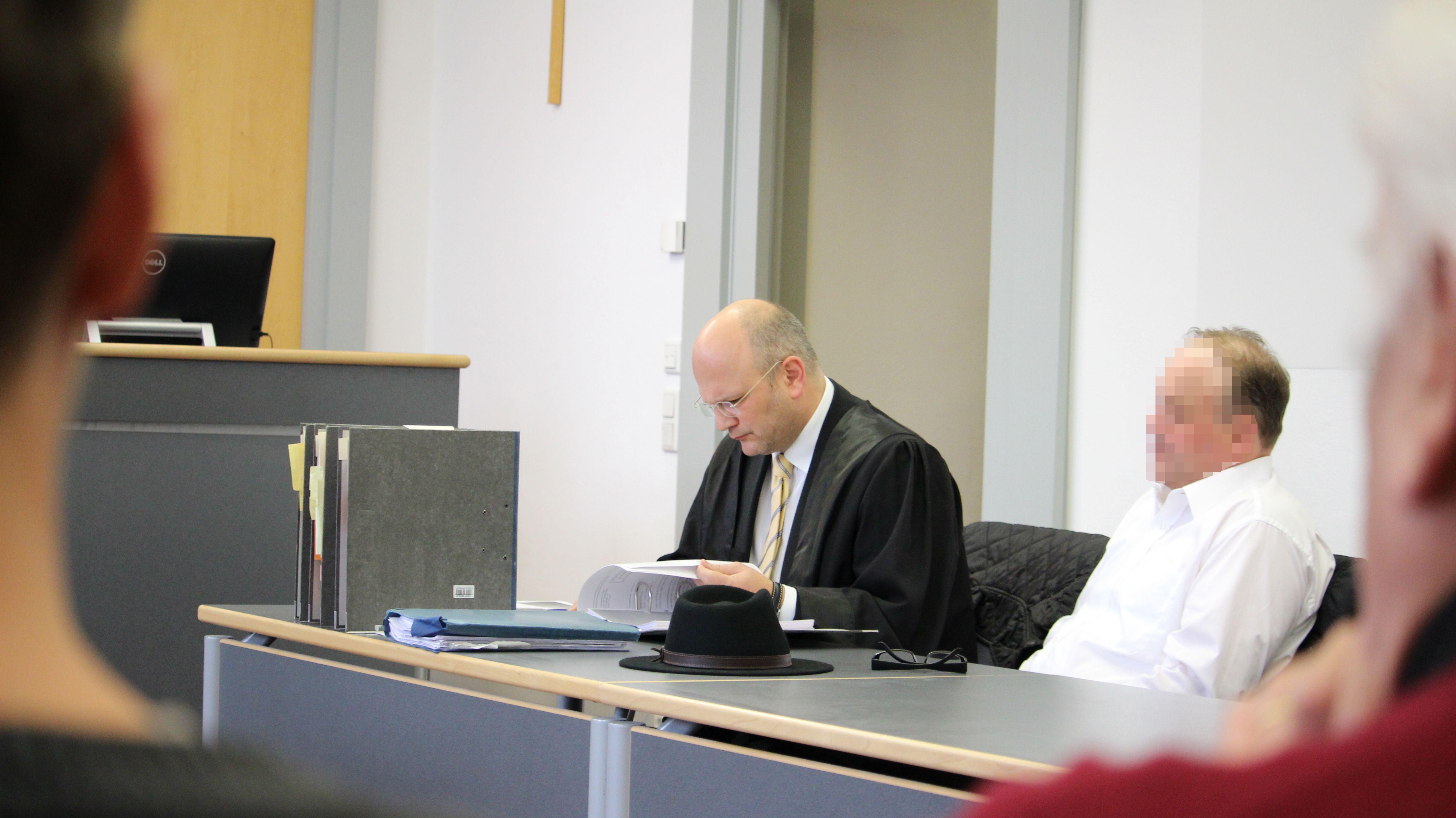 Verteidiger und Angeklagter sitzen an ihrem Tisch im Verhandlungsraum