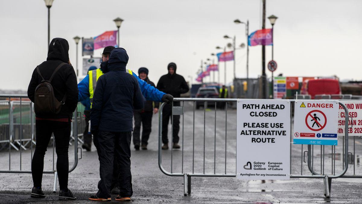 Touristen sprechen mit einem Sicherheitsmitarbeiter in Galways South Park nach der Absage der Eröffnungszeremonie für Galways Jahr als Europäische Kulturhauptstadt im Februar 2020