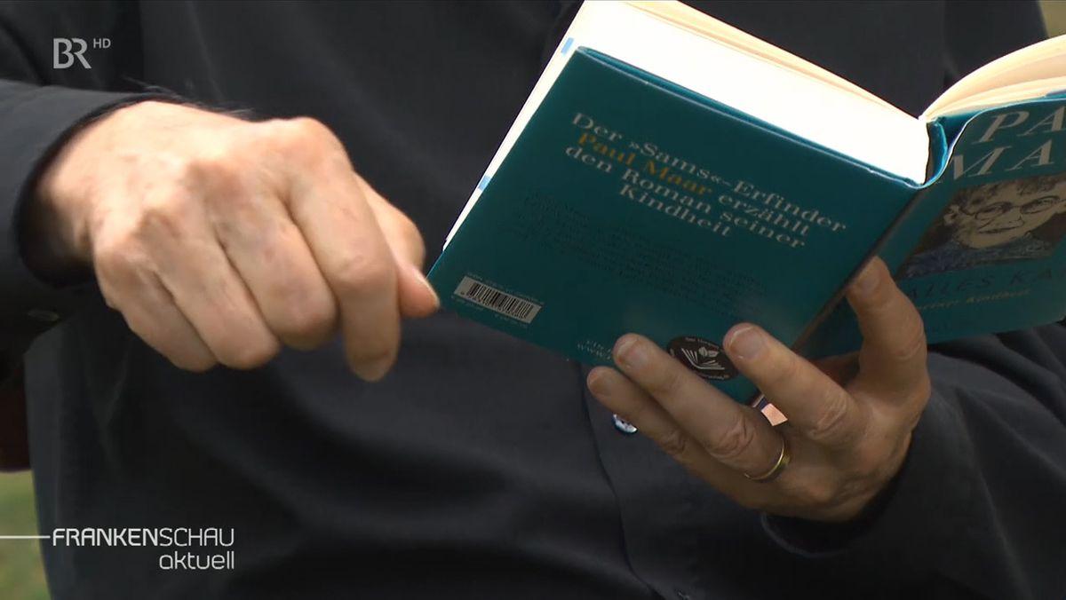 Das neue Buch von Paul Maar wird von zwei Händen aufgeschlagen, um darin zu lesen.