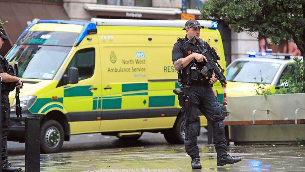 Bewaffnete Polizeibeamte stehen nahe einem Einkaufszentrum vor einem Krankenwagen.