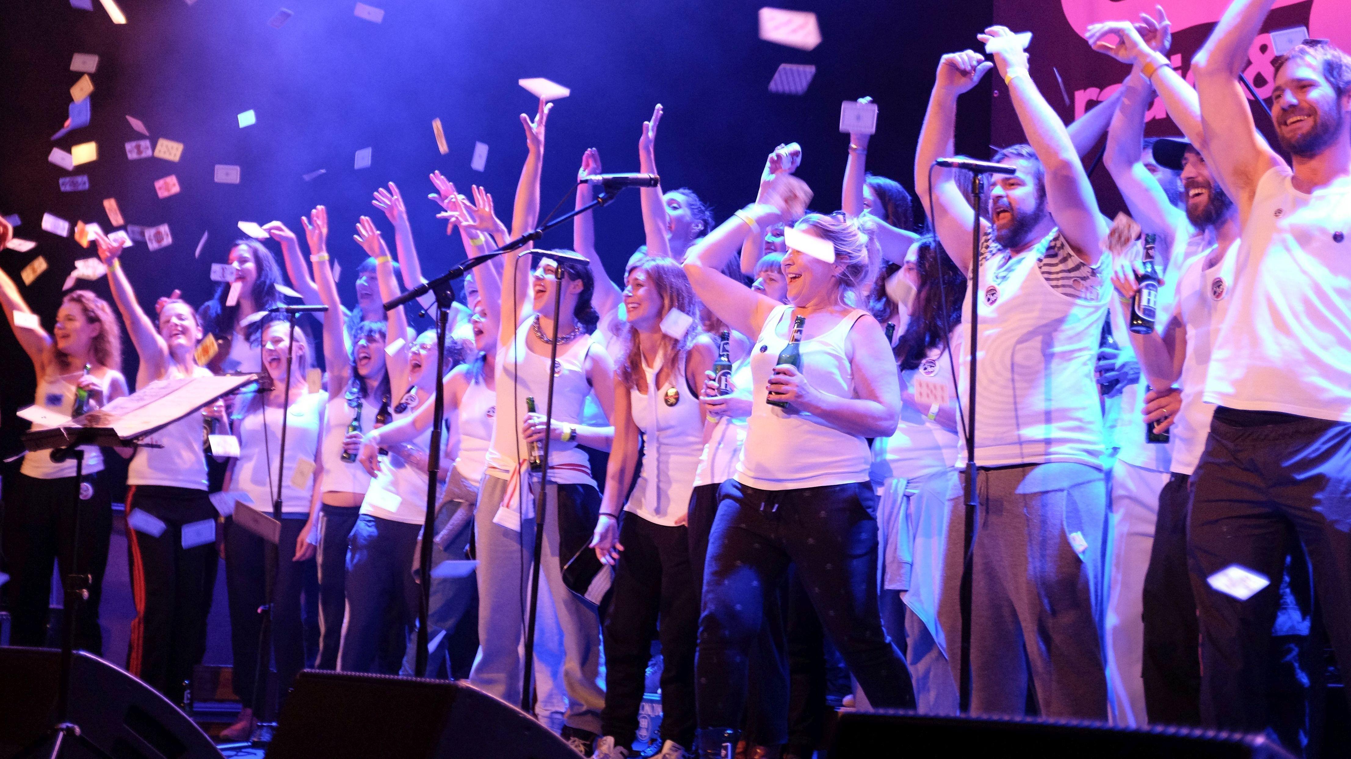 Mitglieder des Münchner Kneipenchors singen auf einer Bühne, gestikulieren wild und werfen Spielkarten in die Luft