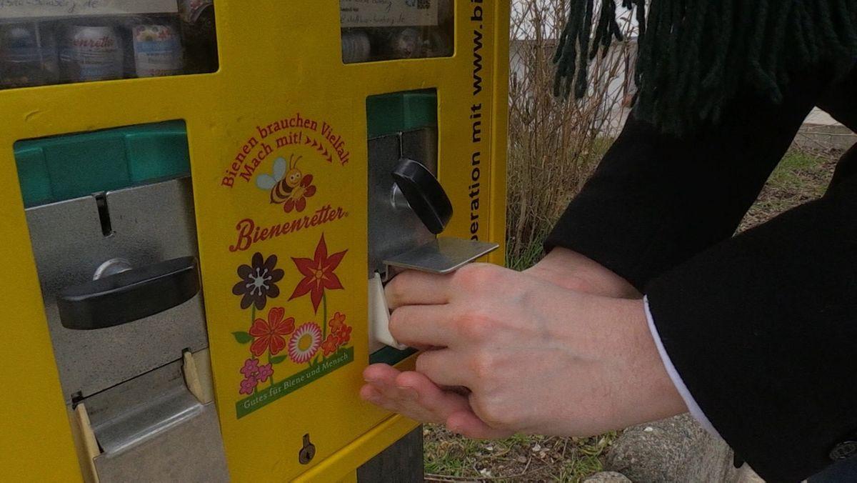 """Aus einem gelben Automaten mit der Aufschrift """"Bienenretter"""" holt ein Mann in Plastikkapsel verpackte Blumensamen."""