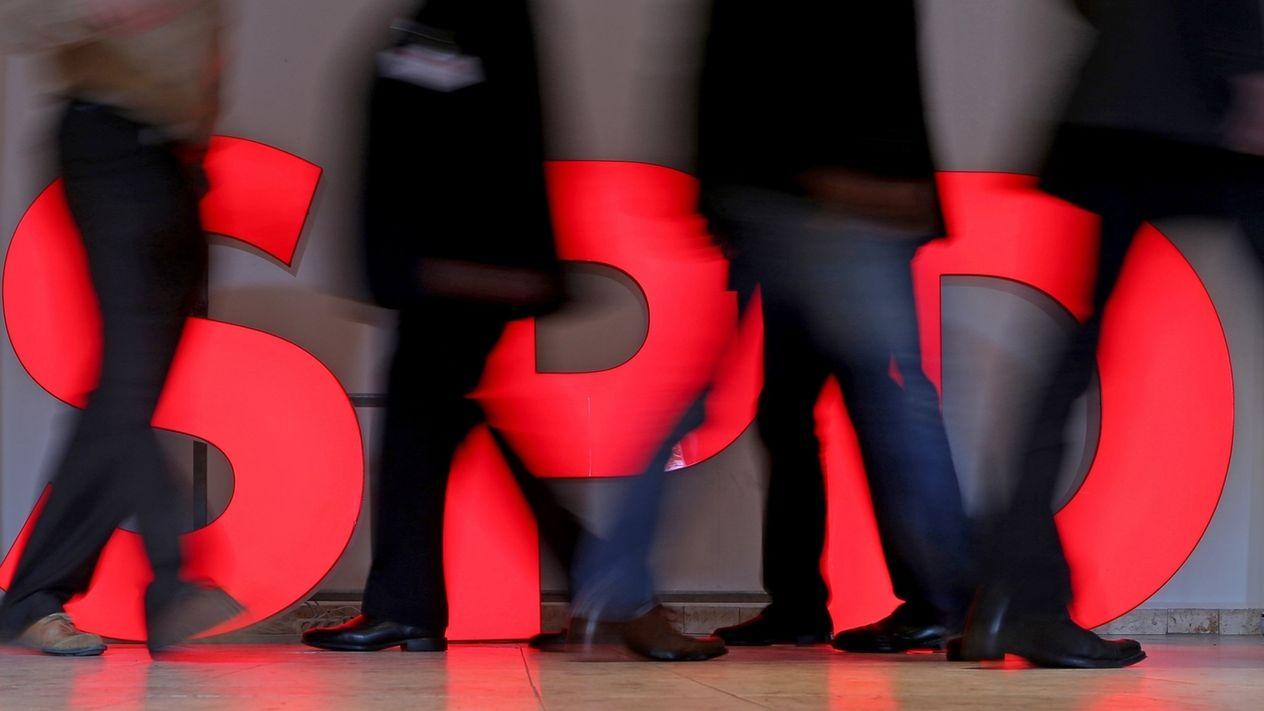 Menschen laufen an einem roten SPD-Schriftzug vorbei, der am Boden steht