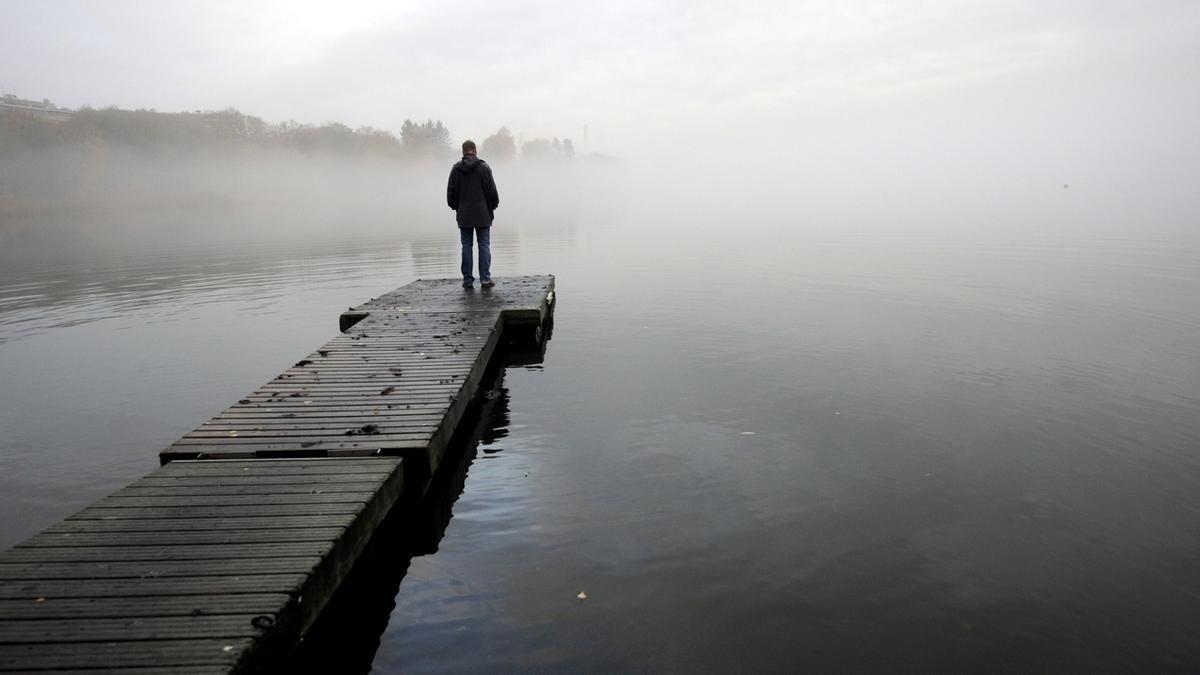 Ein Mann steht auf einem Steg am See bei nebeligen. trüben Wetter.