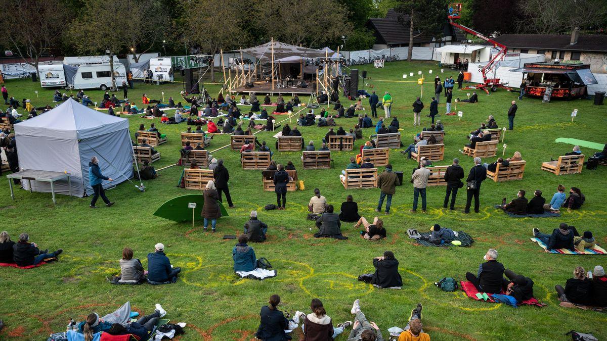 Zuschauer sitzen auf Wiese an markierten Stellen