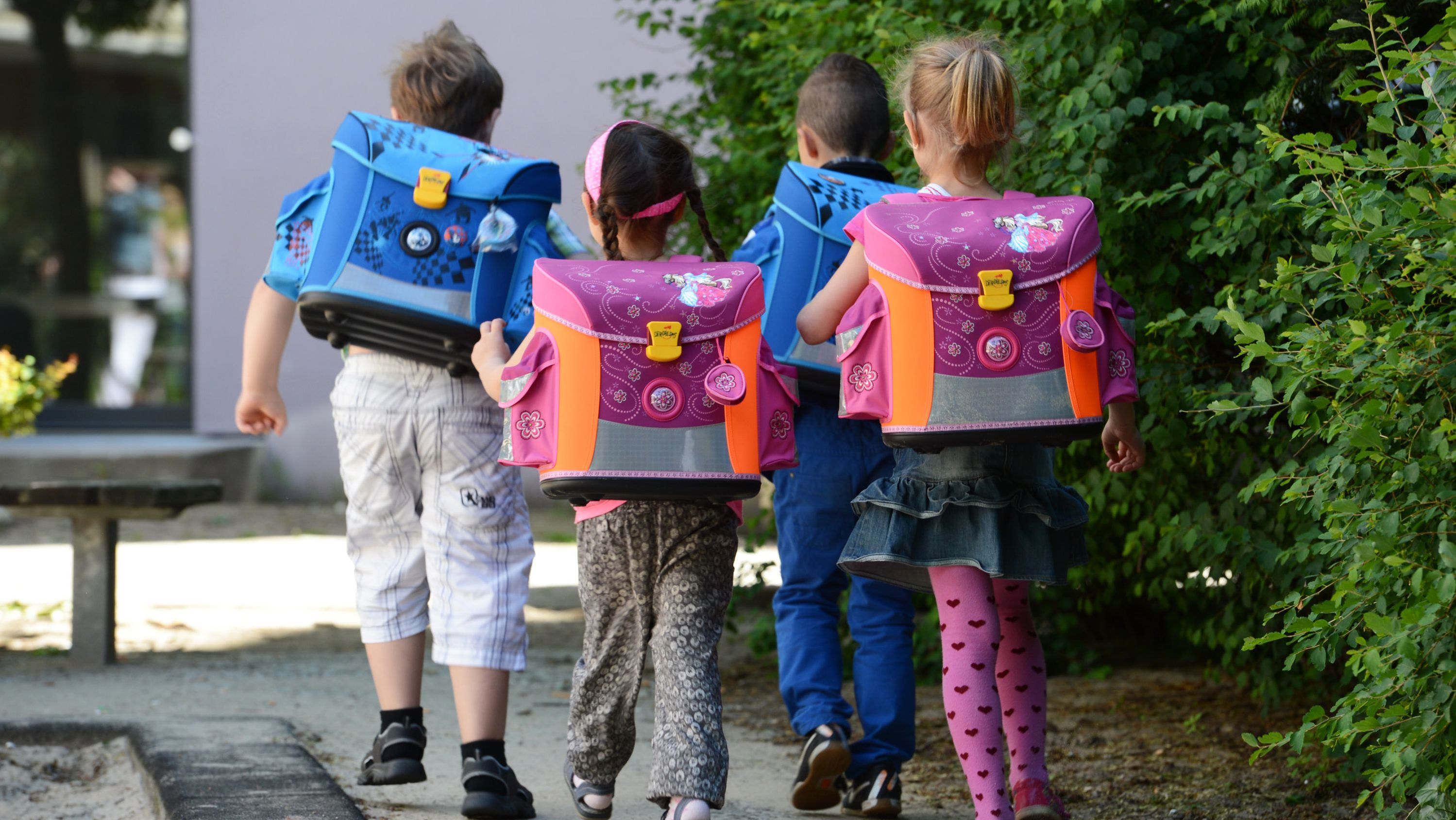 Mehrere Kinder mit Schulranzen gehen einen Fußweg entlang.