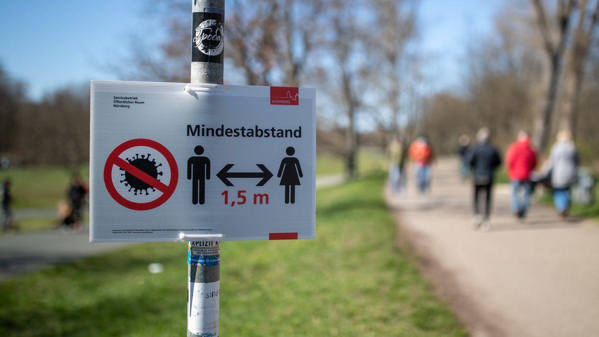 """Nürnberg: """"Mindestabstand 1,5 Meter"""" zwischen Personen wegen des Coronavirus steht auf einem Schild am Rande eines Gehweges."""