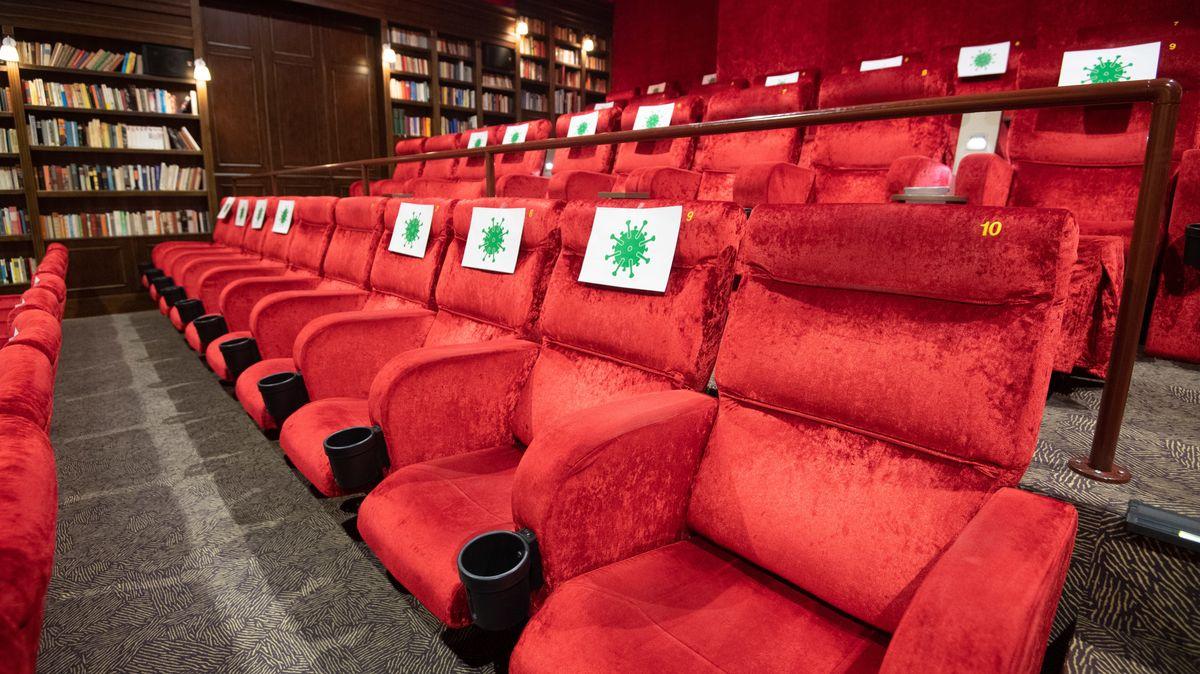 Rote Kinosessel in einem Kinosaal. Im Hintergrund stehen Bücherregale an der Wand.
