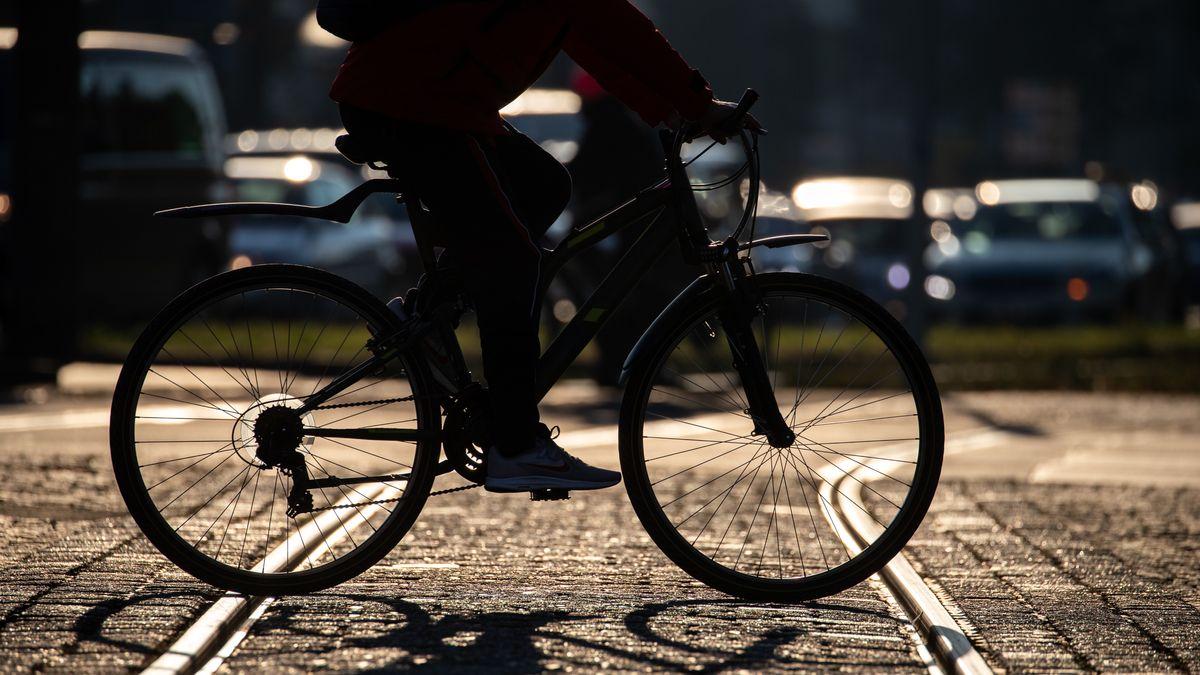 Ein Radfahrer überquert eine leere Straßenbahn-Schiene, während sich im Hintergrund Autos stauen.