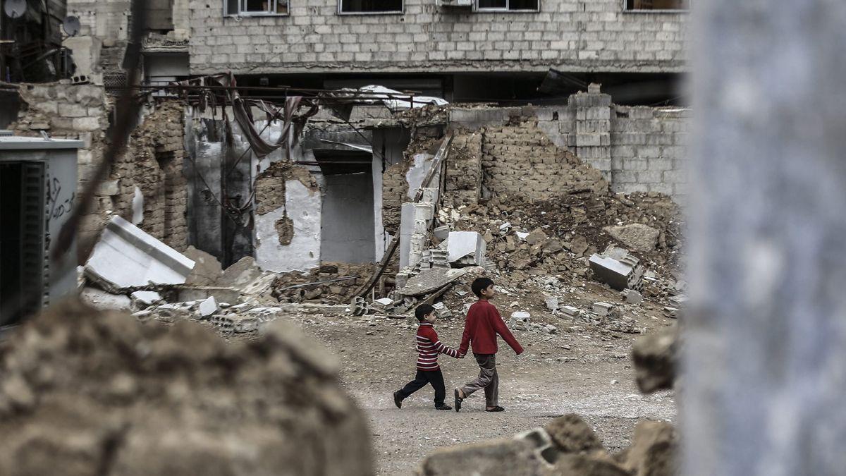 Zwei syrische Jungen gehen in Douma in Syrien an zerstörten Häusern vorbei, Archivbild von 2015.