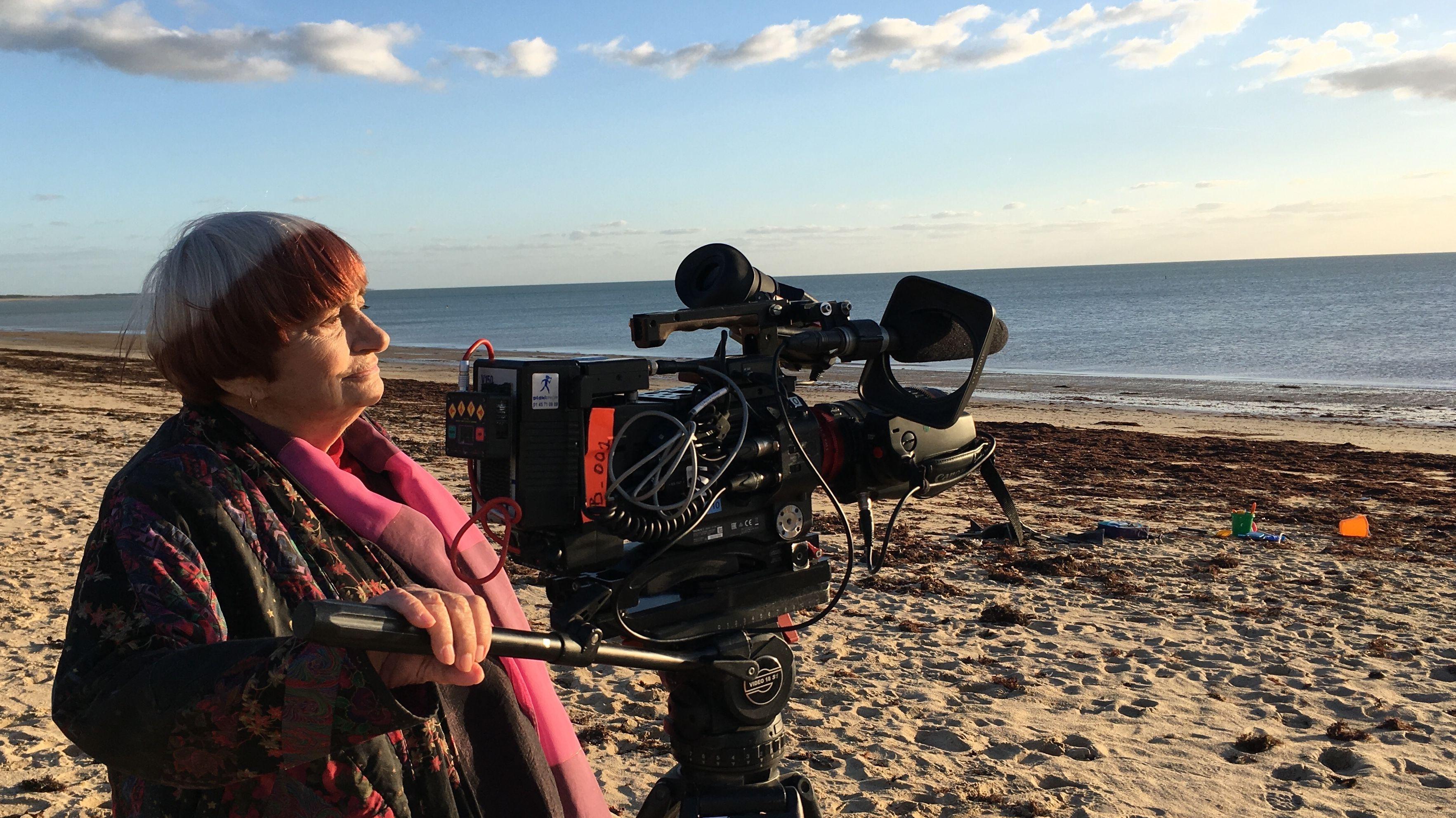Regisseurin Agnès Varda dreht an einem Strand, die Kamera ist aufs Meer gerichtet