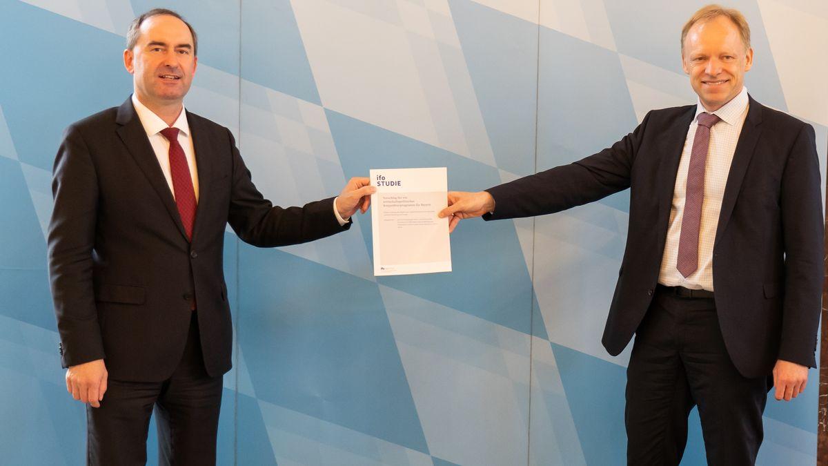 Wirtschaftsminister Aiwanger und ifo-Chef Fuest halten zwischen sich das Gutachten zum Konjunkturprogramm für die bayerische Wirtschaft